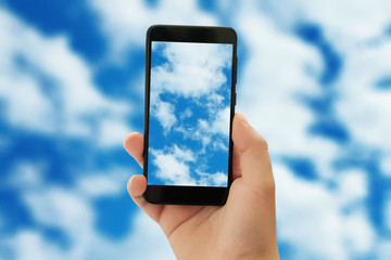 A man holds a phone in his hand and photographs the blue sky with fluffy clouds.