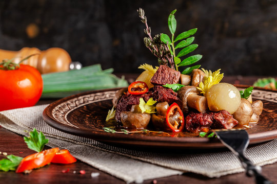French cuisine concept. blanquette of veal with mushrooms, whole stewed onions, carrots and chilli peppers. Serving dishes in the restaurant in a ceramic plate, next to vegetables.