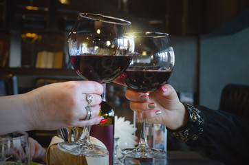 People are clinking wine glasses with red wine and talking a celebration toasts.