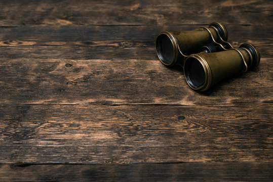Vintage brass binoculars on a brown wooden table background with copy space. Explorer table.