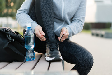 Shot of athletic woman tying she is shoelaces before a run. Wall mural