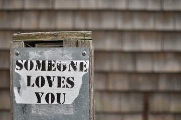 Selective focus, sign on foreground saying Someone Loves You