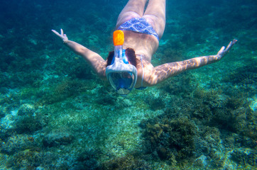 Young woman diving undersea. Snorkel in coral reef of tropical sea. Woman in full-face snorkeling mask.