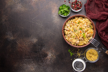 Bulgur with turkey, pork or beef. Eastern dish of rice, delicious traditional food. Stewed meat with grits. Pilaf on dark background