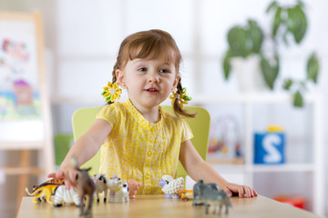 Portrait of joyful child girl toying with statuette of animals in nursery or kindergarten