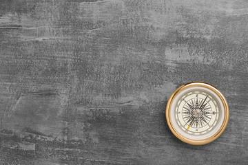 Golden navigational compass on a vintage gray background