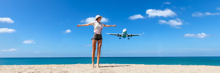 Girl looking at the flying plane above the sea, travel and active lifestyle concept Wall mural