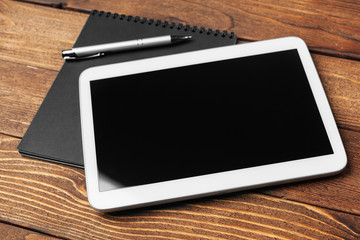 Tablet with notepad on wooden background