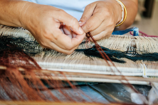Woman hands weaving Thai silk fabric