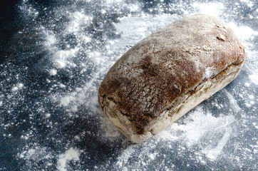 Whole loaf of yeast free bread on flour, dark surface.Concept of backed goods
