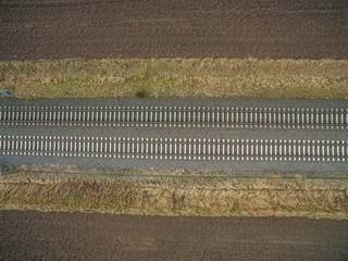 aerial view of railroad tracks in the backcountry between freshly plowed farmland - top view of the train tracks