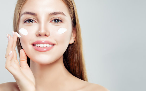 Closeup portrait of beautiful woman with healthy face and skin applying cosmetic cream. Skin care, beauty and facial treatment concept