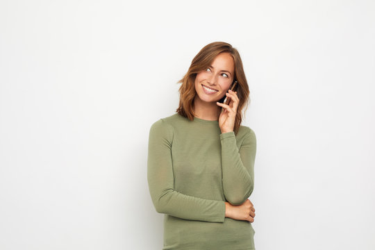 portrait of young smiling woman with mobile phone looking left