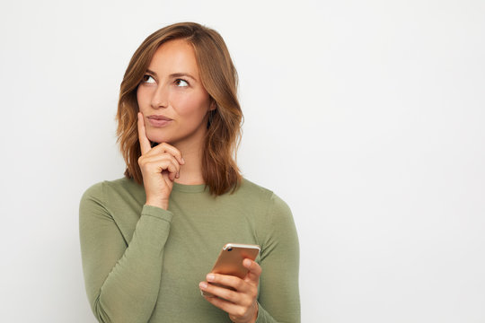 portrait of young woman with mobile phone wondering