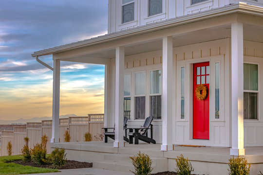Facade of home with red door porch stairs and yard