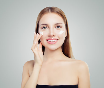 Happy beautiful woman putting cream on healthy skin. Pretty girl with natural makeup applying beauty moisture cosmetics on white background