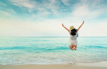 Happy young woman in casual style fashion and straw hat jumping at sand beach. Relaxing, fun, and enjoy holiday at tropical paradise beach with blue sky and white clouds. Girl in summer vacation.