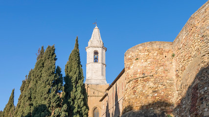 The city walls and the bell tower of the Duomo of Pienza illuminated by the morning sun, Siena, Tuscany, Italy