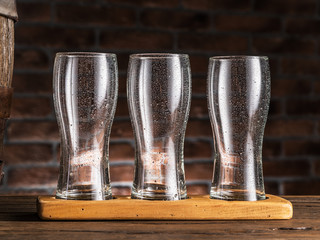 Wall Mural - Empty beer glasses near a cask on wooden table. Craft brewery.