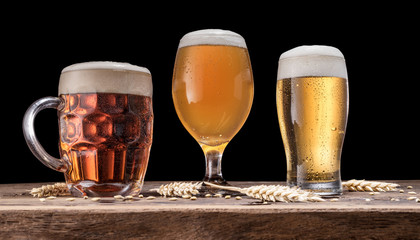 Wall Mural - Glasses of beer on old wooden table. Black background.