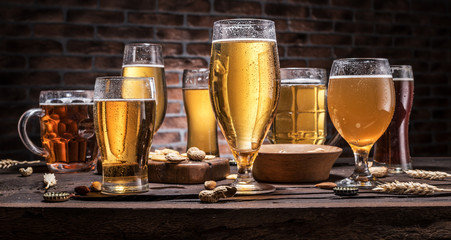 Wall Mural - Cold mugs and glasses of beer on the old wooden table, brick wall at the background. Assortment of beer.