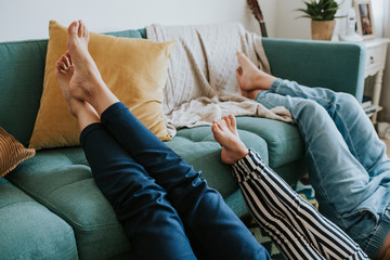 Fototapeta Mom and her kids putting their legs up on the couch obraz