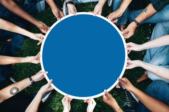 Group of people holding a round blue board