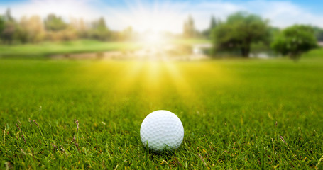 Golf ball on green grass on blurred beautiful landscape of golf course with sunrise,sunset time on background.