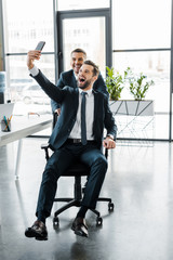 cheerful busimessmen taking selfie and smiling in modern office