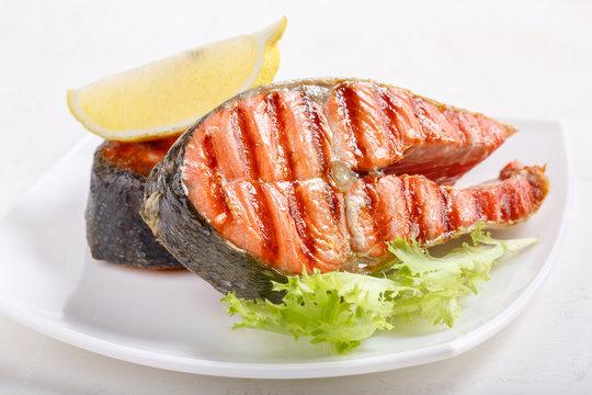 Grilled red salmon steak served with lemon and lettuce on white plate. Sockeye salmon, kokanee salmon or Oncorhynchus nerka.