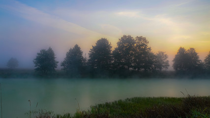 Morning dawn over a forest lake covered with fog. Scarlet paints of dawn make their way through the fog, illuminating the nearest shore