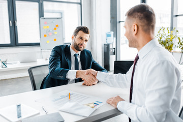 selective focus of businessman shaking hands with coworker in modern office