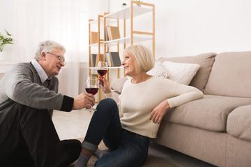 Happy senior couple drinking wine, celebrating anniversary
