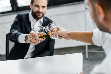 selective focus of businessman toasting glasses of whiskey with coworker