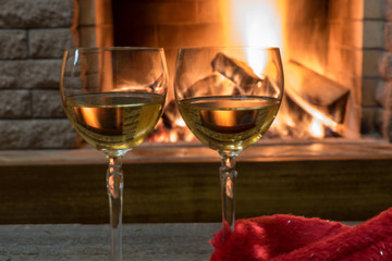 Cozy scene before fireplace with two glasses of wine.