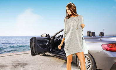 Slim young rich woman and sliver summer car on coast. Sea landscape and blue sky.