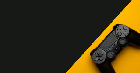 black wireless gamepad on a black and yellow background