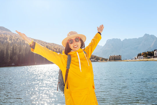 Young happy asian woman with yellow jacket travel at the famous tourist destination in Dolomites mountains - Misurina lake during autumn.