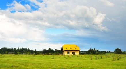Modern farm house in a green field on a summer day