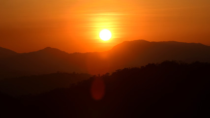 Picture of a sun setting behind a dense forest area followed by mountains.
