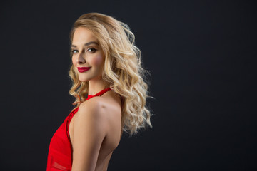 beautiful young girl with graceful figure in a red dress on a black background
