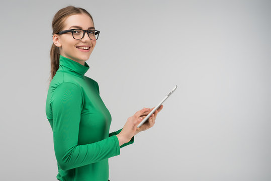 Joyful profile girl holding a tablet in her hands and smiling