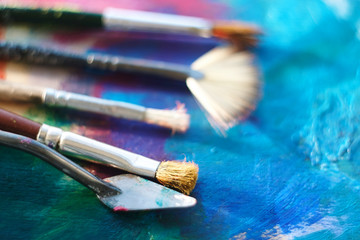 Several tools for drawing: brushes and palette knife lie on the oil-painted palette
