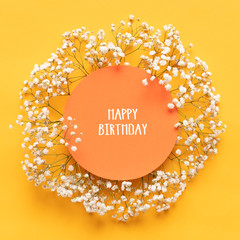 Happy Birthday Card. Flat lay greeting card with beautiful little white flowers on bright yellow paper background.