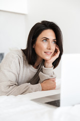 Photo of caucasian woman 30s using laptop, while lying in bed with white linen in bright room