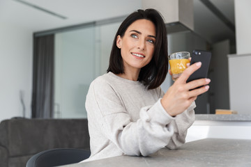 Image of beautiful woman 30s drinking orange juice and using mobile phone, while resting in bright modern room