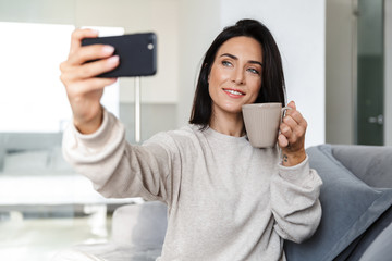 Photo of attractive woman 30s taking selfie on cell phone, while sitting on couch in bright apartment