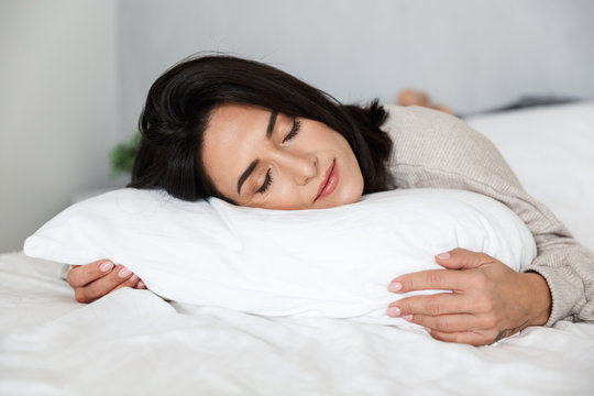 Photo of adult woman 30s sleeping, while lying in bed with white linen at home