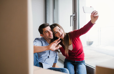 Young couple with cardboard boxes moving in a new home, taking selfie.