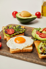 selective focus of cutting board with toasts, scrambled egg, cherry tomatoes and avocado on grey background